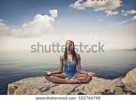 Beautiful african woman sitting on a peak over the sea and meditating - stock photo