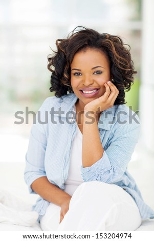 beautiful african woman sitting on bed at home - stock photo