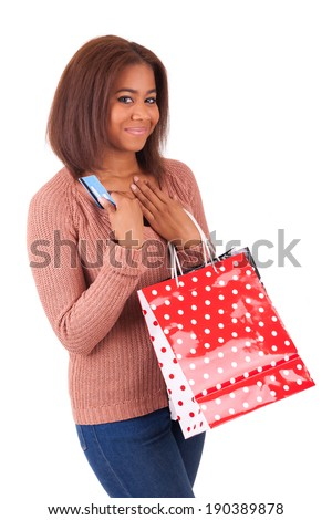 Beautiful african woman smiling holding a credit card and shopping bags - stock photo