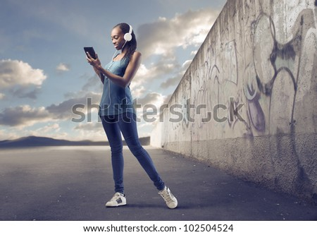 Beautiful african woman using a tablet pc on a city street - stock photo