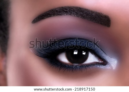 Beautiful African woman wearing eye shadow makeup - stock photo