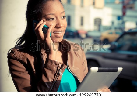 beautiful african young woman using smart phone in the city - stock photo