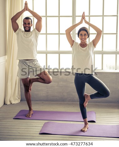 Beautiful Afro American couple is looking at camera and smiling while doing yoga, standing on mat at home