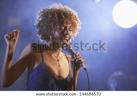 Beautiful Afro American jazz singer on stage - stock photo