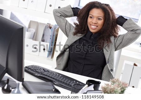 Beautiful afro businesswoman sitting at desk in office, smiling, stretching. - stock photo