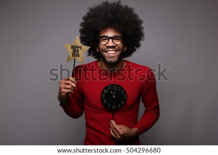Beautiful afro funky man in front of a dark background doing funny faces