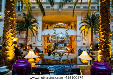Beautiful afternoon tea ceremony in London. Luxury room with palm trees and a silver tea pot standing in the middle of the room. - stock photo