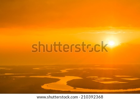 Beautiful air view to the orange sunset sky over the river in the haze.Water on the background is highlighted by sun rays - stock photo