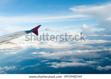 beautiful aircraft wing against blue sky from its windows