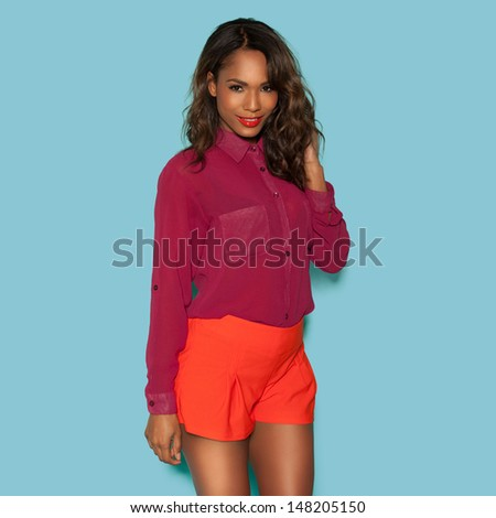 Beautiful alluring young African woman in red shorts and top standing looking seductively at the camera - stock photo