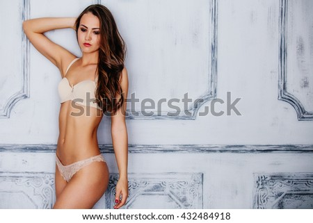 Beautiful alluring young woman in sexy beige lingerie posing in the antique salon. - stock photo