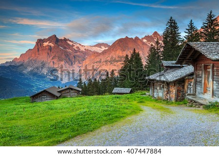 Beautiful alpine landscape,old Swiss traditional wooden hut and magical sunset with Wetterhorn peak in background,Grindelwald,Bernese Oberland,Switzerland,Europe - stock photo