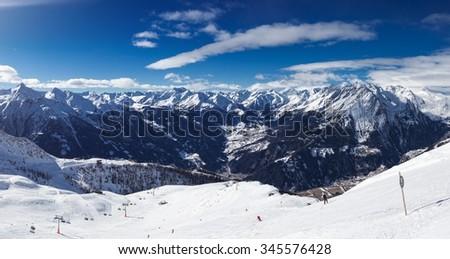 Beautiful alpine mountain range winter panoramic photo. Ski resort in austrian Alps, view at the Grossglockner mountain in Austria - stock photo