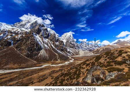 Beautiful alpine scenery in the Himalayas, with snow capped mountains and moraine glacier valley - stock photo