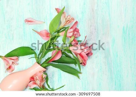 Beautiful alstroemeria in vase on wooden background - stock photo