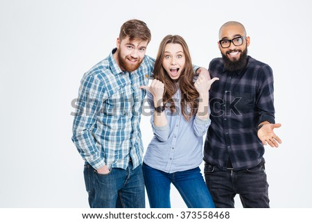 Beautiful amazed young woman standing and pointing on her two bearded handsome friends - stock photo