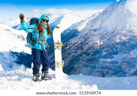 Beautiful amazing day winter mountains. A woman rides snowboard. Sport hike in holidays. Landscape inspiring. Cool fun girl. Blue sky and white snow. Happy hobby