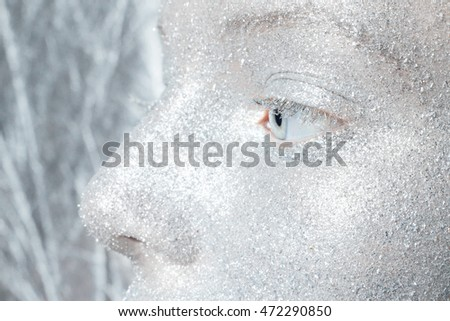 Beautiful, amazing portrait of woman. Unreal make up like a space. Closeup shooting in studio with silver background. Emotion, posing of model. silver glitter.