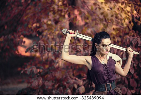 Beautiful amazon warrior in a leather dress with fur and a heavy iron sword in the woods - stock photo