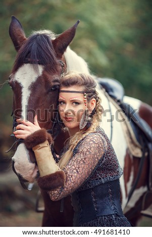 Beautiful amazon warrior with a horse in the woods