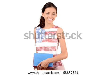 Beautiful American student with USA flag on her blouse holding books and looking to the side. Learn English. Isolated on white. - stock photo