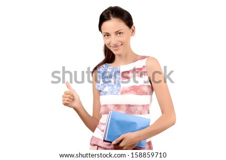 Beautiful American student with USA flag on her blouse holding books and signing thumbs up. Success by learning English. Isolated on white. - stock photo