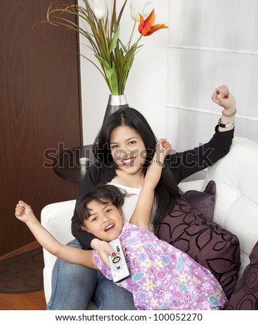 Beautiful American woman and child with TV remote control