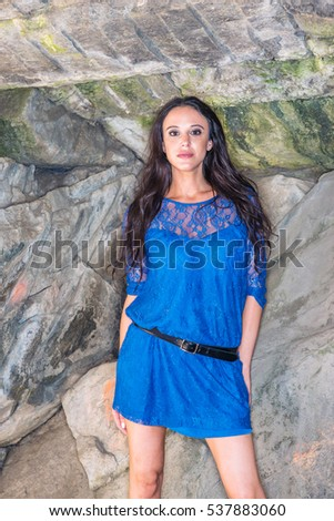 Beautiful American Woman with long black hair, wearing blue dress, belt, causally standing by rocks at Central Park in New York, relaxing. Color filtered look.