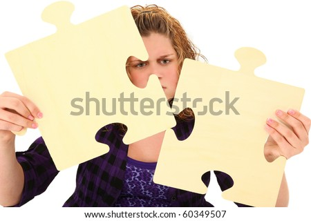 Beautiful american 13 year old teenager with confused face holding giant wooden puzzle pieces over white background. - stock photo