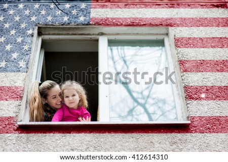 Beautiful american young woman with a child of five years old look out of the window USA and welcome - stock photo