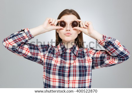 Beautiful amusing teenage girl in checkered shirt covered her eyes with round chocolate candies  - stock photo