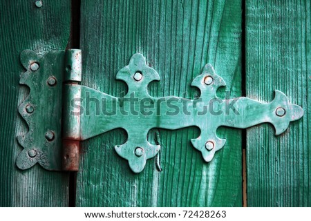 Beautiful ancient door bolt on green collars - stock photo