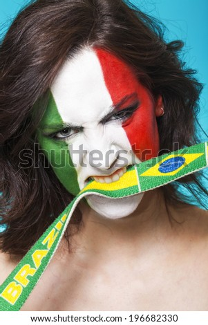 Beautiful and aggressive italian supporter biting the Brazil flag