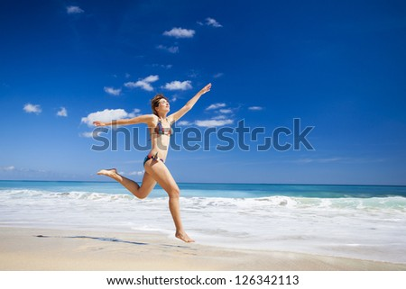 Beautiful and athletic young woman enjoying the summer, jumping in a tropical beach