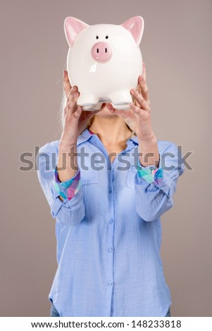 Beautiful and attractive blonde woman holding a piggy bank in front of her head - stock photo