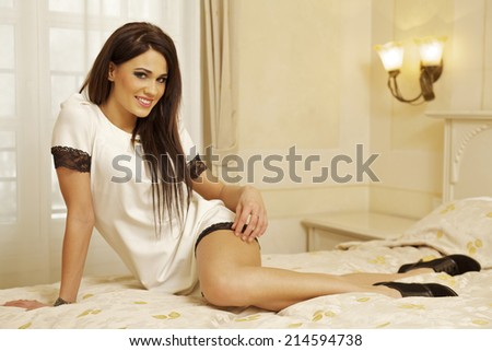 Beautiful and attractive female brunette young adult woman posing in white dress on bed - stock photo