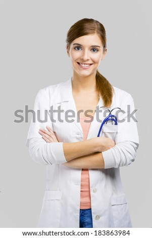 Beautiful and attractive female doctor, isolated over a white background - stock photo