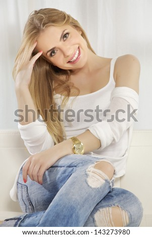 Beautiful and attractive young adult smile blonde woman posing in blue jeans and white shirt sweater on the white sofa