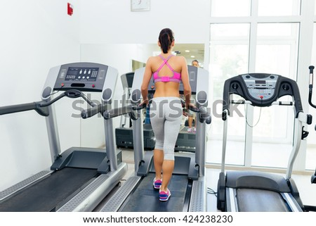 Beautiful and attractive young woman doing exercises at fitness gym. - stock photo