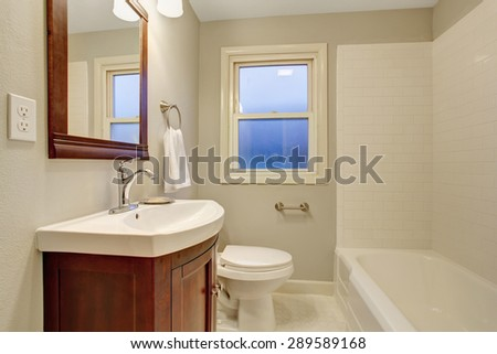 Beautiful, and bright white bathroom with tile floor and bathtub.