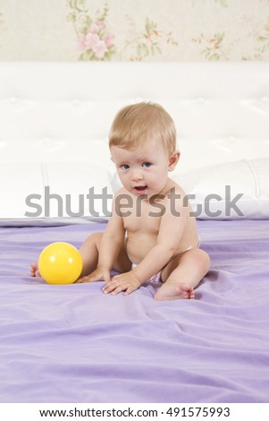 Beautiful and cheerful little girl playing with ball