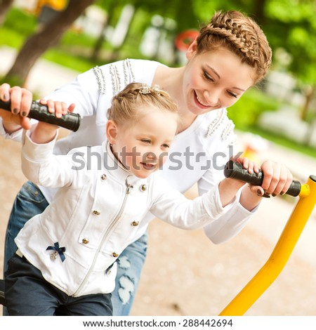 Beautiful and cheerful mother and daughter are walking and playing in the park sunny summer day. - stock photo