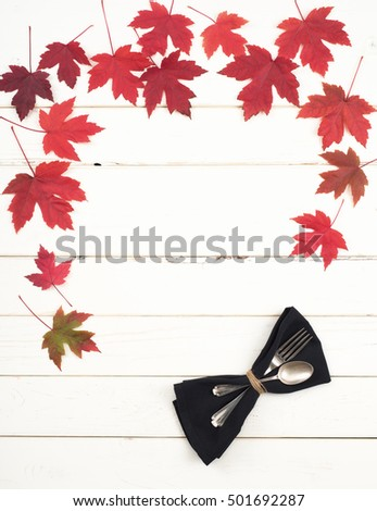 Beautiful and Colorful Fall Red Maple Leaves and place setting on top and sides of Rustic White Board Background with room of space for copy, text, your words.  Slats are horizontal on vertical photo