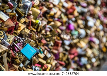 Beautiful and colorful love locks attached together for love wishes in a bridge in Paris France