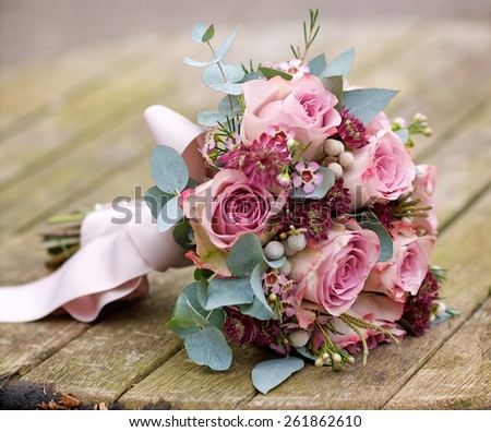 Beautiful and colourful bouquet of flowers over wood table - stock photo