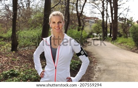 Beautiful and confident young fitness woman outdoors. Caucasian female runner out in forest for training. - stock photo