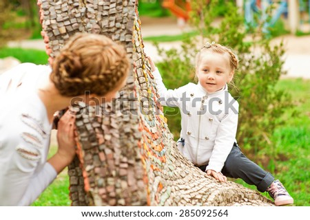 Beautiful and cute girl playing with her mother in a park a sunny summer day. - stock photo