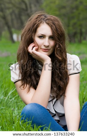 Beautiful and cute girl thoughtfully sitting on the green grass - stock photo