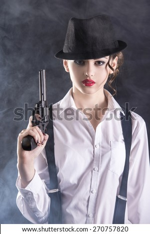 Beautiful and dangerous. Young female gangster holding the gun. isolated on dark background. - stock photo