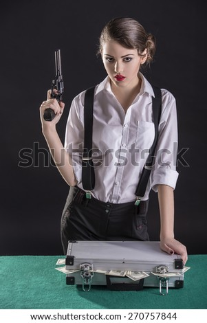 Beautiful and dangerous. Young female gangster holding the gun. isolated on dark background. On the green table a bag of cash. - stock photo